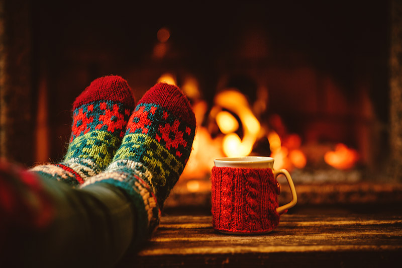 Cozy socks next to fire with warm mug wrapped with its own sweater